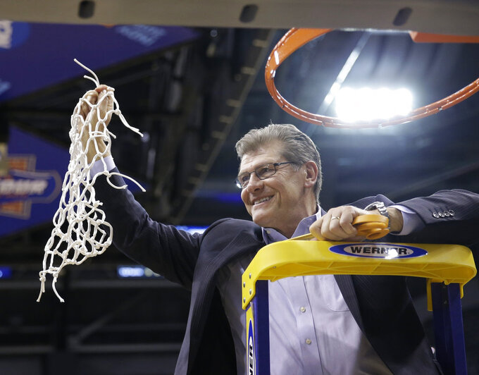 FILE - In this Tuesday, April 5, 2016, file photo, Connecticut head coach Geno Auriemmac celebrates by cutting down the net following Connecticut's 82-51 championship victory over Syracuse at the women's Final Four in the NCAA college basketball tournament in Indianapolis. Auriemma's 11 titles are one more than UCLA's John Wooden for the most ever in Division I basketball. (AP Photo/AJ Mast, File)