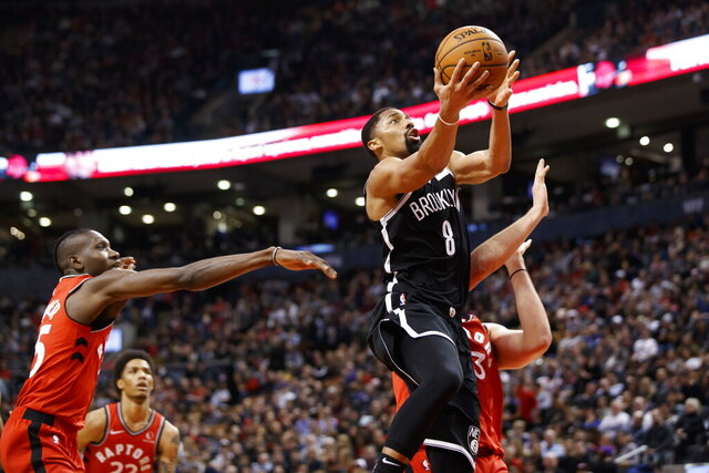 Brooklyn Nets guard Spencer Dinwiddie drives to the hoop against Toronto Raptors forward Chris Boucher, left, and center Marc Gasol, hidden, during the first half of an NBA basketball game in Toronto, Saturday, Dec. 14, 2019. (Cole Burston/The Canadian Press via AP)