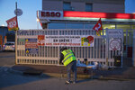 A worker on strike at the Fos-sur-Mer ESSO refinery gathers at the refinery entrance in Marseille southern France, Tuesday, Jan. 7, 2020. French President Emmanuel Macron says he wants to reach a
