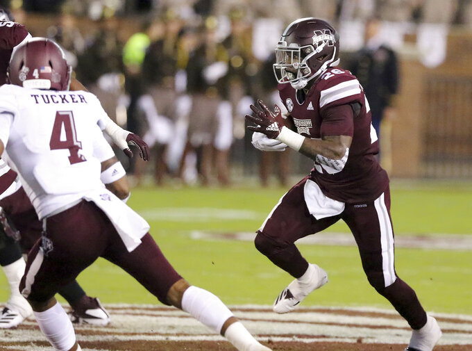 Mississippi State running back Aeris Williams (26) looks for running room to avoid a tackle by Texas A&M defensive back Derrick Tucker (4) during the first half of their NCAA college football game on Saturday, Oct. 27, 2018, in Starkville, Miss. (AP Photo/Jim Lytle)