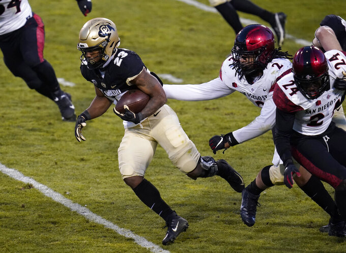 Colorado running back Jarek Broussard, left, drives for a short gain past San Diego State defensive lineman Keshawn Banks (2) and linebacker Segun Olubi (24) in the first half of an NCAA college football game Saturday, Nov. 28, 2020, in Boulder, Colo. (AP Photo/David Zalubowski)