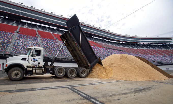"FILE - Workers begin turning Bristol Motor Speedway in Bristol, Tenn., into a dirt track in this Thursday, Jan. 7, 2021, file photo. NASCAR is being heavily promoted by a broadcast partner as about to embark on ""The Best Season Ever"" and on paper that could be true. NASCAR this year will race on dirt for the first time since 1970, the schedule includes a whopping seven road courses and five venues new to the Cup Series. Michael Jordan and Pitbull are among new team owners entering the sport in 2021 and Chase Elliott, NASCAR's most popular driver, is the reigning champion. (David Crigger/Bristol Herald Courier via AP, File)"