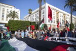 People hold a large Palestinian flag during a protest against normalizing relations with Israel, in Rabat, Morocco, Friday, Sept. 18, 2020. Despite a government ban on large gatherings aimed at preventing the spread of the coronavirus, scores of Moroccans staged a protest outside parliament building in the capital Rabat on Friday to denounce Arab normalization agreements with Israel. (AP Photo/Mosa'ab Elshamy)