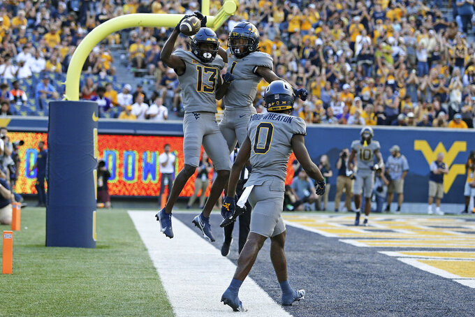 West Virginia wide receivers Sam James (13) and Winston Wright Jr. (1) celebrate after a touchdown against Long Island during the first half of an NCAA college football game in Morgantown, W.Va., Saturday, Sept., 11, 2021. (AP Photo/Kathleen Batten)