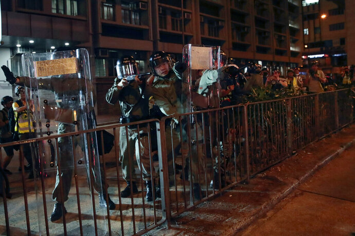 Riot police aim at protesters outside Mong Kok police station during a mod protests in Hong Kong on Wednesday, Sept. 4, 2019. Hong Kong Chief Executive Carrie Lam has announced the government will formally withdraw an extradition bill that has sparked months of demonstrations in the city, bowing to one of the protesters' demands. The bill would have allowed Hong Kong residents to be sent to mainland China for trials. It sparked massive protests that have become increasingly violent and caused the airport to shut down earlier this month. (AP Photo/Jae C. Hong)