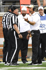 Wake Forest head coach Dave Clawson, front right, talks to a referee during the first half of an NCAA college football game against Boston College, Thursday, Sept. 13, 2018, in Winston-Salem, N.C. (AP Photo/Woody Marshall)