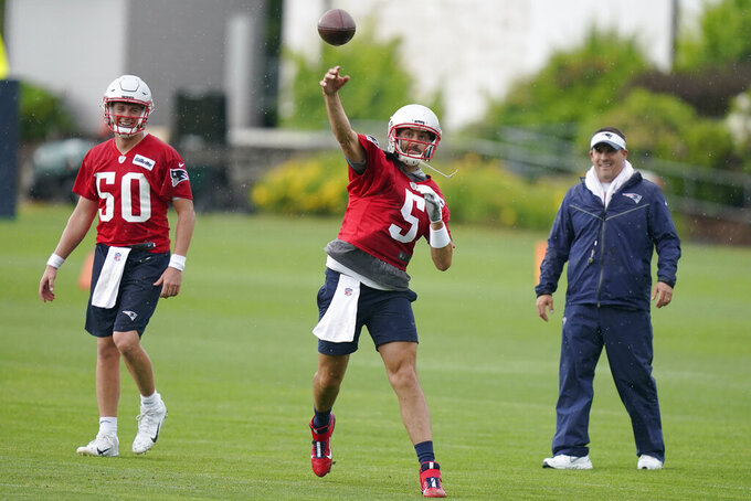 New England Patriots quarterbacks Mac Jones (50) and Brian Hoyer (5) work out on the field during an NFL football practice as offensive coordinator Josh McDaniels, right, looks on, Monday, June 14, 2021, in Foxborough, Mass. (AP Photo/Steven Senne)
