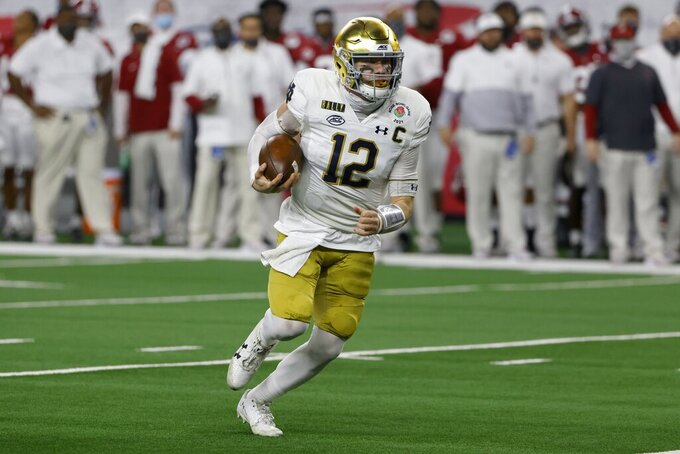 Notre Dame quarterback Ian Book (12) runs the ball in the first half of the Rose Bowl NCAA college football game against Alabama in Arlington, Texas, Friday, Jan. 1, 2021. (AP Photo/Ron Jenkins)