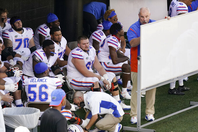 Florida players listen to a coach during halftime at an NCAA college football game between the Florida and Vanderbilt Saturday, Nov. 21, 2020, in Nashville, Tenn. (AP Photo/Mark Humphrey)