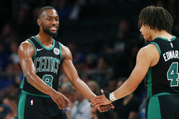 Boston Celtics guard Carsen Edwards (4) congratulates Celtics guard Kemba Walker (8) as Walker returns to the bench during the second half of an NBA basketball game in New York, Saturday, Oct. 26, 2019. Walker scored 32 points to help the Celtics defeat the New York Knicks 118-95. (AP Photo/Kathy Willens)
