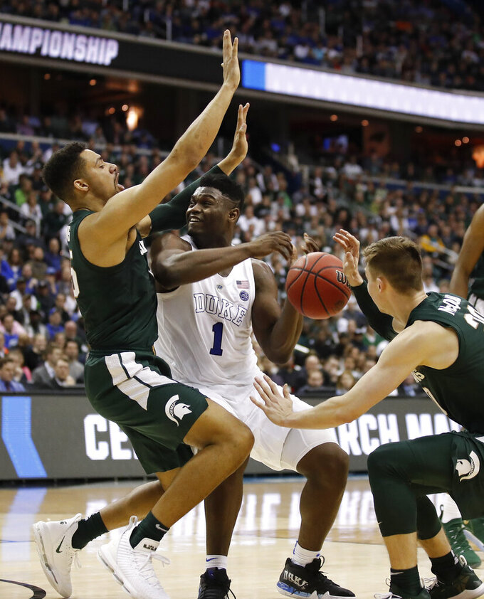 Duke forward Zion Williamson (1) loses control of the ball while going up against Michigan State forward Kenny Goins, left, and guard Matt McQuaid, right, during the second half of an NCAA men's East Regional final college basketball game in Washington, Sunday, March 31, 2019. (AP Photo/Alex Brandon)