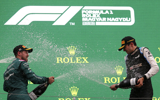 Race winner, Alpine driver Esteban Ocon of France, right, celebrates on the podium with second placed Aston Martin driver Sebastian Vettel of Germany after the Hungarian Formula One Grand Prix, at the Hungaroring racetrack in Mogyorod, Hungary, Sunday, Aug. 1, 2021. (Florion Goga/Pool via AP)