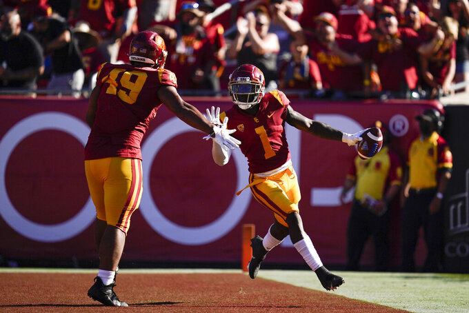 Southern California safety Greg Johnson (1) celebrates with defensive lineman Tuli Tuipulotu (49) after intercepting a pass and running it in for a touchdown during the second half of an NCAA college football game against the San Jose State Saturday, Sept. 4, 2021, in Los Angeles. (AP Photo/Ashley Landis)