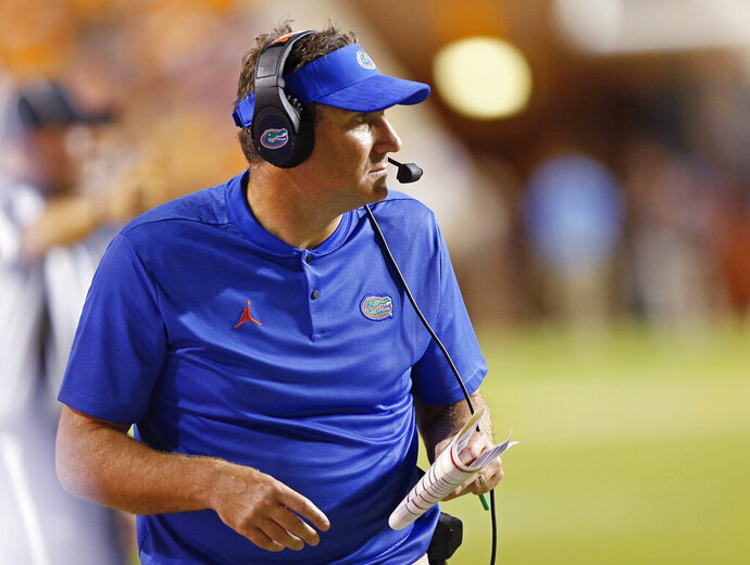 "FILE - In this Sept. 22, 2018, file photo, Florida coach Dan Mullen watches during the first half of the team's NCAA college football game against Tennessee in Knoxville, Tenn. Mullen's strong, personal beliefs about violence toward women haven't resulted in a zero-tolerance policy for his program. Although Mullen expressed disappointment in having two players and a staff member accused of violence toward women in the past month, he acknowledged Wednesday, May 15, 2019, that he'd ""be hypocritical if you look at my history to say to that is a 100 percent deal."" Mullen's past experiences explain why safety Brian Edwards and Otis Yelverton, an assistant director of player personnel, remain part of the program. (AP Photo/Wade Payne, File)"