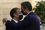 French President Emmanuel Macron, left, welcomes Prime Minister Kyriakos Mitsotakis Tuesday, Sept. 28, 2021 at the Elysee Palace in Paris. The leaders of Greece and France are expected to announce a major, multibillion-euro deal in Paris on Tuesday involving the acquisition by Greece of at least six French-built warships, Greek state ERT TV reported. (AP Photo/Francois Mori)