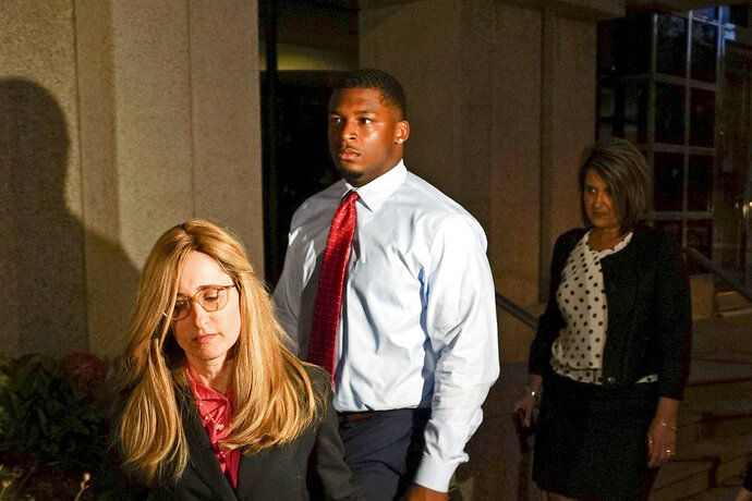 FILE – In this Sept. 14, 2017, file photo, Ma'lik Richmond, center, of Steubenville, Ohio, and his attorney Susan Stone, left, walk out of U.S. District Court in Youngstown, Ohio. An Ohio judge has scheduled a Thursday, April 19, 2018, hearing about whether Richmond, a high school and college football player convicted as a juvenile of raping a 16-year-old girl during an alcohol-fueled party, should be removed from the state's sex offender listings. (AP Photo/Dake Kang, File)