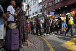Tourists watch as protesters march in an area popular with Chinese tourists for its pharmacies and cosmetic shops, in Hong Kong, Saturday, July 13, 2019. Several thousand people marched in Hong Kong on Saturday against traders from mainland China in what is fast becoming a summer of unrest in the semi-autonomous Chinese territory. (AP Photo/Kin Cheung)