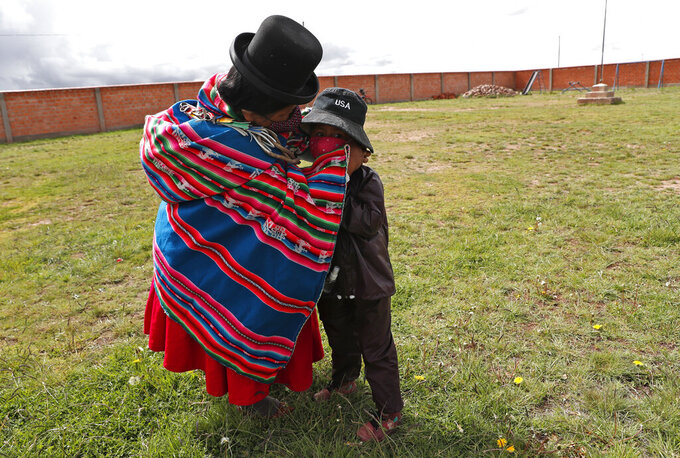 An Aymara Indigenous mother fixes her son's mask before he enters Jancohaqui Tana school, wearing his new protective uniform amid the COVID-19 pandemic during the first week back to school amid the COVID-19 pandemic, near Jesus de Machaca, Bolivia, Thursday, Feb. 4, 2021. (AP Photo/Juan Karita)