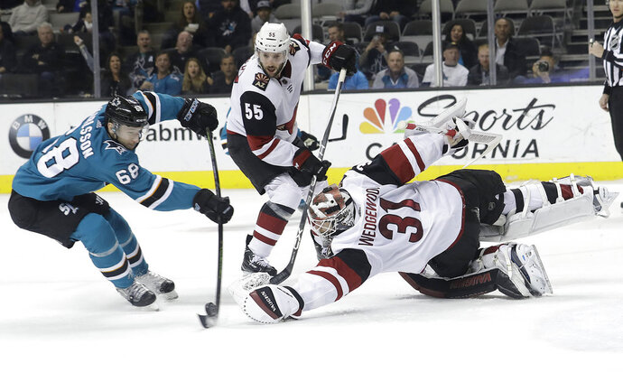 Arizona Coyotes goaltender Scott Wedgewood (31) reaches for the puck in front of San Jose Sharks right wing Melker Karlsson (68), from Sweden, during the second period of an NHL hockey game in San Jose, Calif., Tuesday, Feb. 13, 2018. (AP Photo/Jeff Chiu)