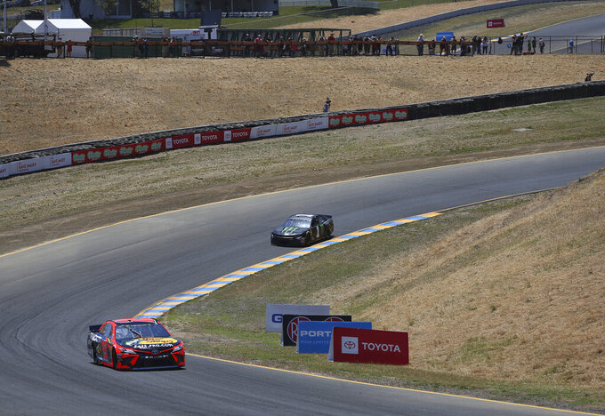 Martin Truex, Jr., front, and Kurt Busch drive around the Carousel during practice for the NASCAR Cup Series auto race at Sonoma Raceway on Friday, June 21, 2019, in Sonoma, Calif. (Christopher Chung/The Press Democrat via AP)