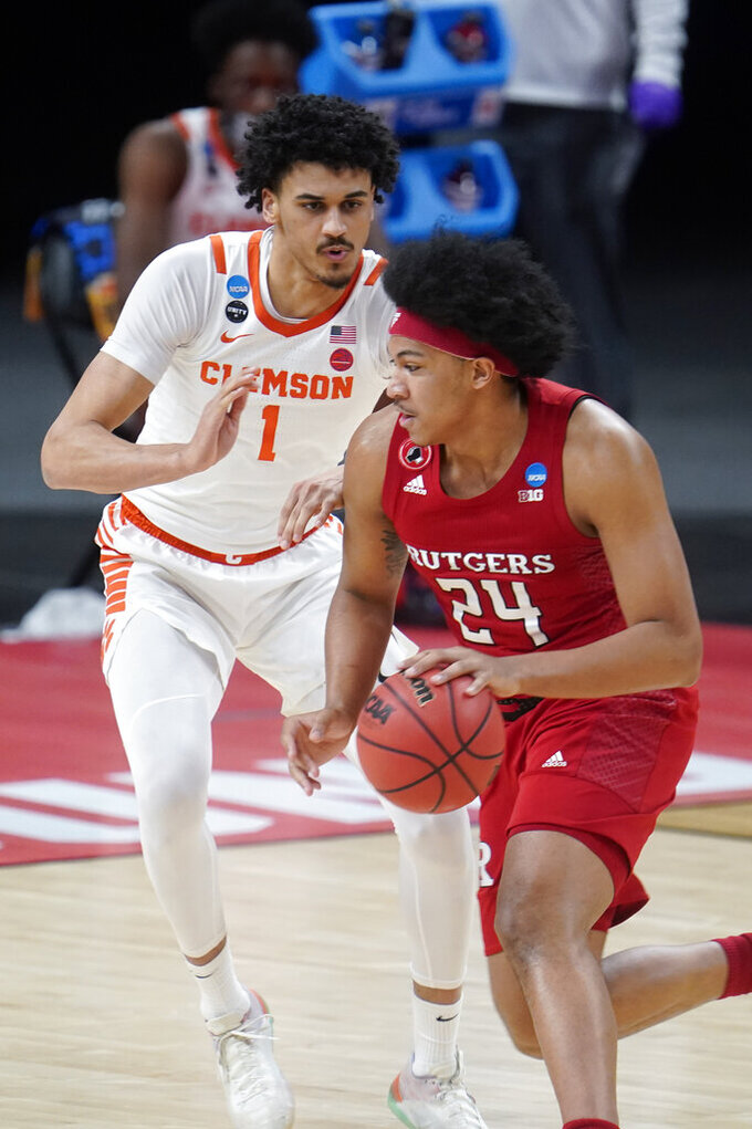 Rutgers guard Ron Harper Jr. (24) drives on Clemson forward Jonathan Baehre (1) during the first half of a men's college basketball game in the first round of the NCAA tournament at Bankers Life Fieldhouse in Indianapolis, Friday, March 19, 2021. (AP Photo/Paul Sancya)
