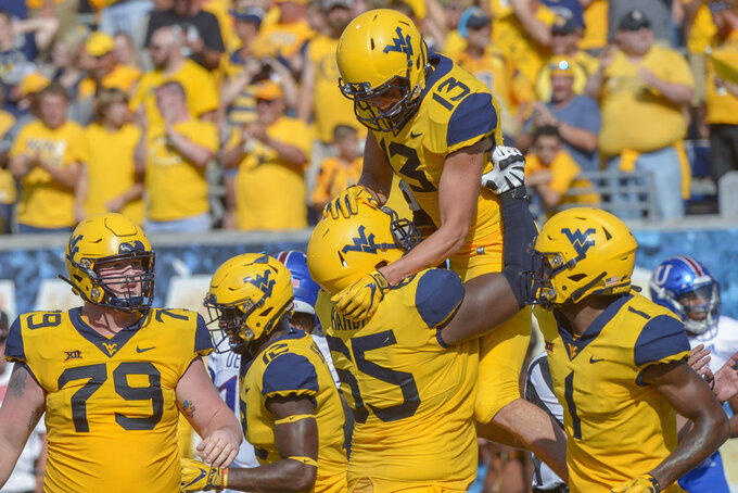 West Virginia offensive lineman Isaiah Hardy (65) lifts up wide receiver David Sills V (13) after Sills scored a touchdown during the second half of an NCAA college football game against Kansas in Morgantown, W. Va., Saturday Oct. 6, 2018. (Craig Hudson/Charleston Gazette-Mail via AP)