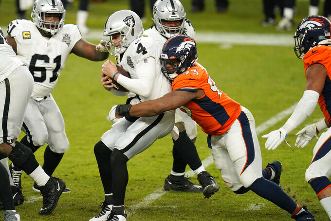 Denver Broncos defensive end Dre'Mont Jones (93) tackles Las Vegas Raiders quarterback Derek Carr (4) during the second half of an NFL football game, Sunday, Jan. 3, 2021, in Denver. (AP Photo/Jack Dempsey)