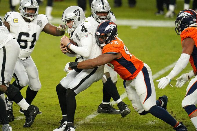 Denver Broncos defensive end Dre'Mont Jones (93) tackles Las Vegas Raiders quarterback Derek Carr (4) during the second half of an NFL football game, Sunday, Jan. 3, 2021, in Denver. (AP Photo/Jack Dempsey)