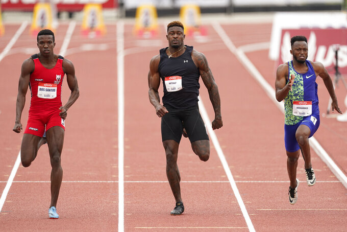 Seattle Seahawks wide receiver DK Metcalf, center, competes in the second heat of the men's 100-meter dash prelim during the USATF Golden Games at Mt. San Antonio College Sunday, May 9, 2021, in Walnut, Calif. At left is Felipe Bardi Dos Santos and at right is Abdullah Mohammed. (AP Photo/Ashley Landis)
