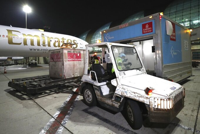 A Pfizer-BioNTech COVID-19 coronavirus vaccines shipment is offloaded from an Emirates Airlines Boing 777 that arrived from Brussels at Dubai International Airport in Dubai, United Arab Emirates, early Sunday, Feb. 21, 2021. As the coronavirus pandemic continues to clobber the aviation industry, Emirates Airlines, the Middle East's biggest airline is seeking to play a vital role in the global vaccine delivery effort. (AP Photo/Kamran Jebreili)