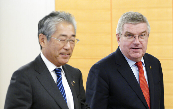 FILE - In this Nov. 30, 2018, file photo, International Olympic Committee (IOC) President Thomas Bach, right, escorts Japanese Olympic Committee (JOC) President Tsunekazu Takeda during an IOC Executive Board meeting in Tokyo. France's financial crimes office says International Olympic Committee member Takeda is being investigated for corruption related to the 2020 Tokyo Olympics. The National Financial Prosecutors office says Takeda, the president of the Japanese Olympic Committee, was placed under formal investigation for