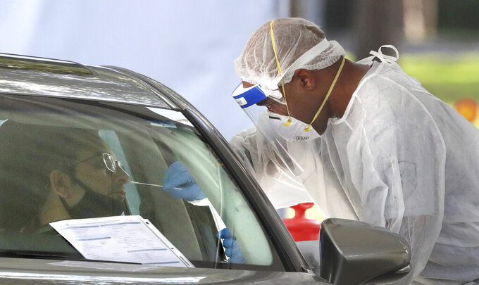 A medical professional applies a nasal swab during testing at the Orange County Health Services COVID-19 drive-thru site at Barnett Park in Orlando, Fla., Thursday, Oct.  29, 2020. The free tests are available 8am to 1pm daily at the park adjacent to the Central Florida Fairgrounds on West Colonial Drive. (Joe Burbank /Orlando Sentinel via AP)