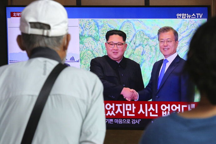 "People watch a TV showing a file image of North Korean leader Kim Jong Un, left, and South Korean President Moon Jae-in during a news program at the Seoul Railway Station in Seoul, South Korea, Friday, Sept. 25, 2020. North Korean leader Kim apologized Friday over the killing of a South Korea official near the rivals' disputed sea boundary, saying he's ""very sorry"" about the incident he called unexpected and unfortunate, South Korean officials said.  (AP Photo/Ahn Young-joon)"