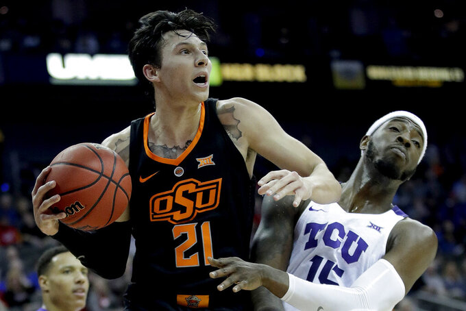 Oklahoma State's Lindy Waters III, left, beats TCU's JD Miller to a rebound during the first half of an NCAA college basketball game in the Big 12 men's tournament Wednesday, March 13, 2019, in Kansas City, Mo. (AP Photo/Charlie Riedel)