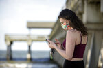 A Tybee Island, Ga., resident uses her phone to text a friend near the pier on the south side of Tybee beach while wearing a handmade mask Saturday, April 4, 2020. On Friday, Gov. Bryan Kemp opened the state's outdoor space by signing an executive order that allows people to exercise outside, with social distancing of at least six feet because of the coronavirus outbreak. (Stephen B. Morton/Atlanta Journal-Constitution via AP)