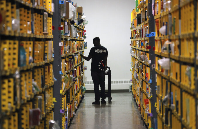 FILE- In this Dec. 21, 2016, file photo an employee of Amazon PrimeNow stacks shelves for customers making last minute holiday orders at a distribution hub in New York. Amazon's plans to pay employees at least $15 an hour is putting pressure on small business owners, even those that aren't retailers who directly compete with the huge company. (AP Photo/Bebeto Matthews, File)