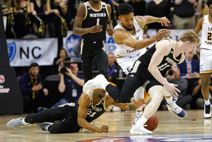 Wofford guard Tray Hollowell (21), East Tennessee State forward Jeromy Rodriguez (11) and Wofford guard Trevor Stumpe (15) scramble for the ball during the first half of an NCAA men's college basketball championship game for the Southern Conference tournament, Monday, March 9, 2020, in Asheville, N.C. (AP Photo/Kathy Kmonicek)