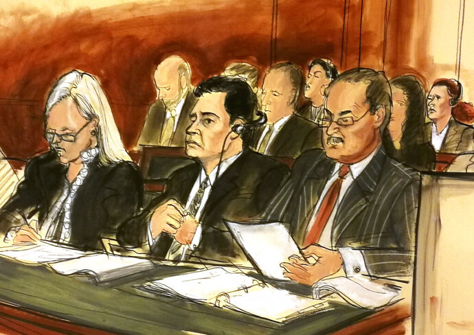 In this courtroom sketch Mehmet Hakan Atilla, second from left, listens to the judge during his sentencing, flanked by his attorneys Cathy Fleming, left, and Victor Rocco as Atilla's wife, upper right, listens to the proceedings Wednesday, May 16, 2018, in New York. U.S. District Judge Richard Berman imposed a sentence of 32 months in prison on the Turkish banker convicted of helping Iran evade U.S. sanctions. (Elizabeth Williams via AP)