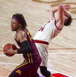 Nebraska guard Thorir Thorbjarnarson, right, reacts after getting hit on the head by the elbow of Minnesota's Brandon Johnson (23) during the second half of an NCAA college basketball game Saturday, Feb. 27, 2021, in Lincoln, Neb. (Francis Gardler/Lincoln Journal Star via AP)