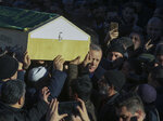 Turkey's President Recep Tayyip Erdogan helps to carry the coffin of a victim after an earthquake hit Elazig, eastern Turkey, Friday, during the funeral procession for the quake victims Salih Civelek and Aysegul Civelek, Saturday, Jan. 25, 2020. Rescuers continued searching for people buried under the rubble of collapsed buildings while emergency workers and security forces distributed tents, beds and blankets in the affected areas. Mosques, schools, sports halls and student dormitories were opened for hundreds who left their homes after the quake. (Presidential Press Service via AP, Pool)