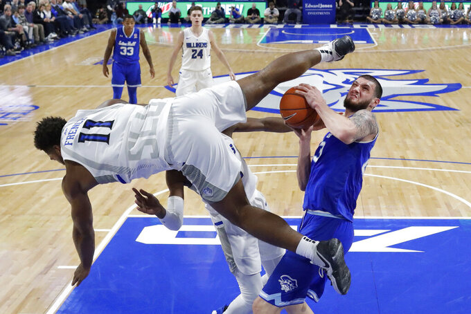 Saint Louis' Hasahn French (11) flips over Seton Hall's Sandro Mamukelashvili, right, as Mamukelashvili heads to the basket during the second half of an NCAA college basketball game Sunday, Nov. 17, 2019, in St. Louis. Seton Hall won 83-66. (AP Photo/Jeff Roberson)
