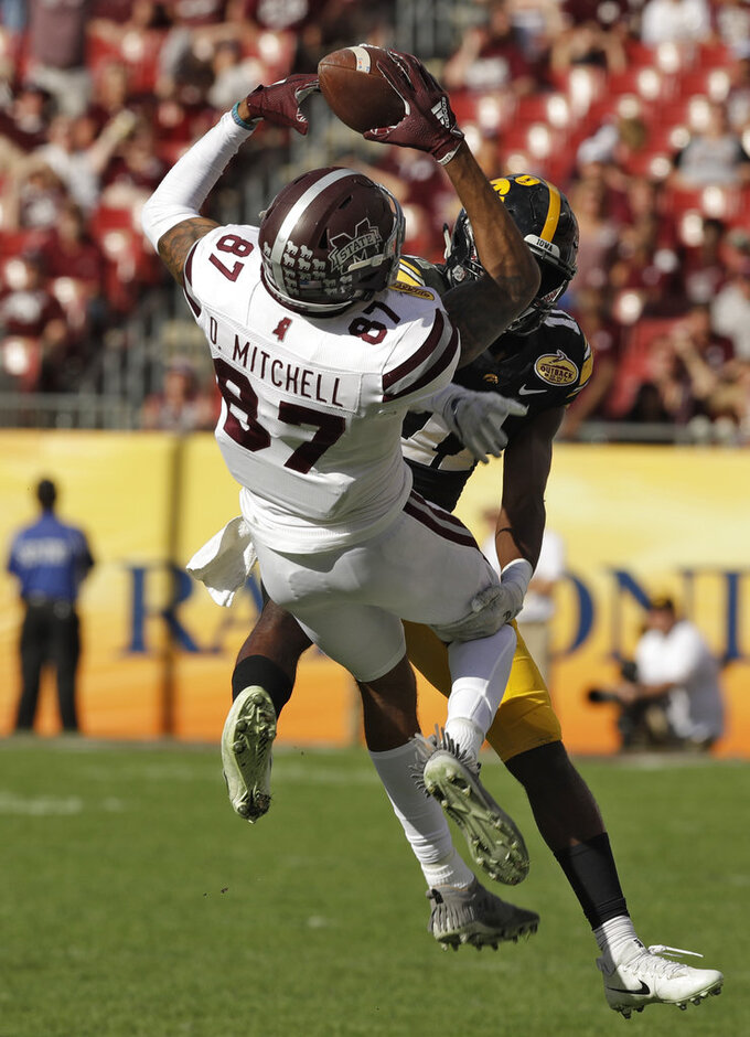 Mississippi State wide receiver Osirus Mitchell (87) makes a catch in front of Iowa defensive back Michael Ojemudia during the second half of the Outback Bowl NCAA college football game Tuesday, Jan. 1, 2019, in Tampa, Fla. (AP Photo/Chris O'Meara)