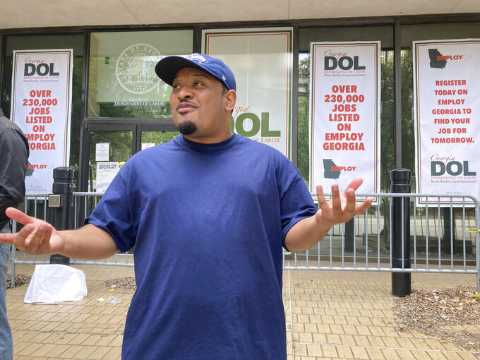 Marcellus Rowe, 29, talks about the prospect of losing federal unemployment aid at a protest outside the Georgia Department of Labor, Thursday, June 24, 2021, in Atlanta. Rowe says he's not sure how he will pay his rent and utilities without the aid. (AP Photo/Jeff Amy)