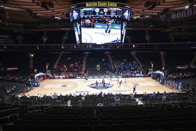 FILE - In this March 12, 2020, file photo, fans watch as Creighton takes on St. John's in an NCAA college basketball game in the quarterfinals of the Big East Conference tournament at Madison Square Garden in New York. As more than 300 teams prepare to start a season that will look nothing like any before it, the conversation is not so much about who will be cutting nets at the end of March Madness, as whether anyone will cut nets at all. (AP Photo/Mary Altaffer, File)