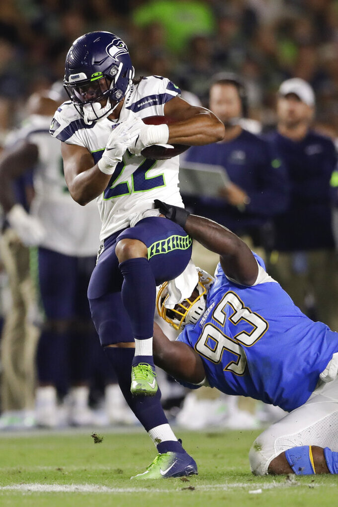 Seattle Seahawks running back C.J. Prosise is tackled by Los Angeles Chargers defensive tackle Justin Jones during the first half of an NFL preseason football game Saturday, Aug. 24, 2019, in Carson, Calif. (AP Photo/Gregory Bull)