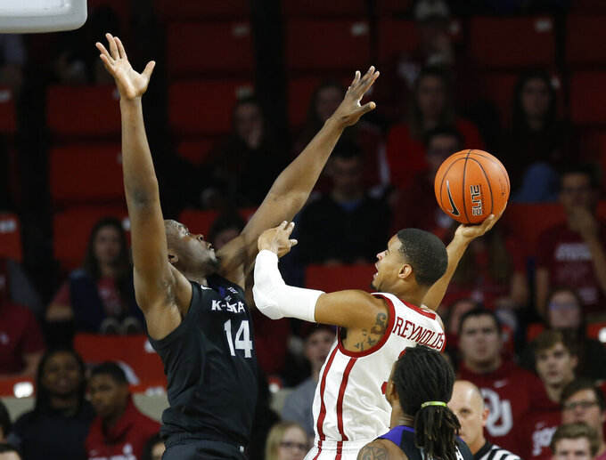 Kansas State forward Makol Mawien (14) defends as Oklahoma guard Miles Reynolds, right, shoots during the first half of an NCAA college basketball game in Norman, Okla., Wednesday, Jan. 16, 2019. (AP Photo/Sue Ogrocki)