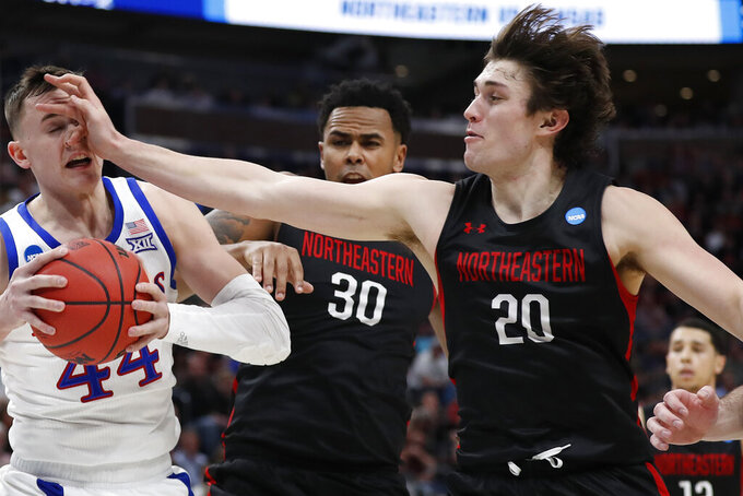 Kansas forward Mitch Lightfoot (44) takes a hand to the face by Northeastern guard Bolden Brace (20) in the first half during a first round men's college basketball game in the NCAA Tournament, Thursday, March 21, 2019, in Salt Lake City. (AP Photo/Jeff Swinger)