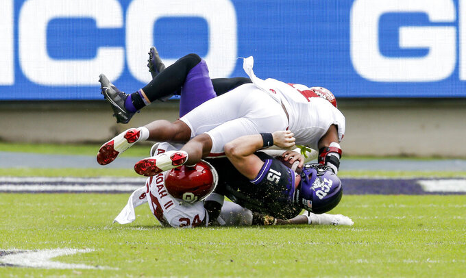 Oklahoma linebackers Nik Bonitto (11) and Brian Asamoah (24) sack TCU quarterback Max Duggan (15) during the second half of an NCAA college football game, Saturday, Oct. 24, 2020, in Fort Worth, Texas.  (AP Photo/Brandon Wade)