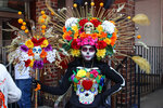 A woman dressed as a catrina poses for a photo at the Wilmington Hispanic Festival and Parade on Sunday, Sept. 12, 2021, in Wilmington, Del. People danced in the streets and watched from their doorsteps as passing parade floats serenaded Wilmington's majority-Hispanic Hilltop neighborhood on Sunday with the booming tunes of bachata and reggaetón.  (José Ignacio Castañeda Perez/The News Journal via AP)