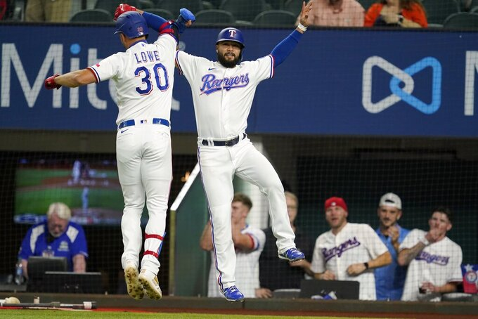 Texas Rangers' Nathaniel Lowe (30) and Isiah Kiner-Falefa, right, celebrate after Lowe hit a two-run home run that scored Kiner-Falefa during the first inning of the team's baseball game against the Houston Astros in Arlington, Texas, Tuesday, Sept. 14, 2021. (AP Photo/Tony Gutierrez)